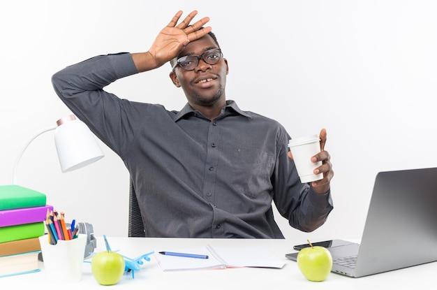 Felice giovane studente afro-americano in occhiali ottici seduto alla scrivania con gli strumenti della scuola mettendo la mano sulla testa e tenendo il bicchiere di carta isolato sul muro bianco