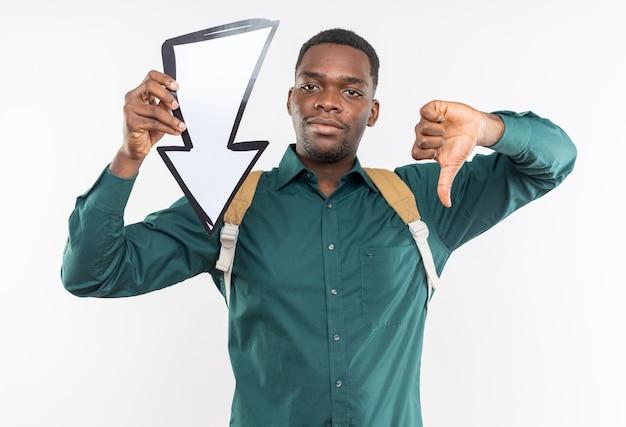 Felice giovane studente afroamericano con lo zaino che tiene la freccia e punta verso il basso isolato sul muro bianco con spazio di copia