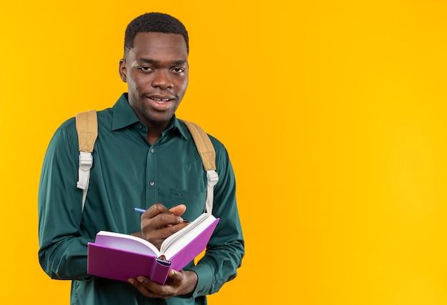 Soddisfatto giovane studente afroamericano con zaino che tiene libro e matita