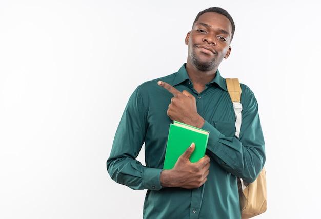 Soddisfatto giovane studente afroamericano con zaino che tiene in mano un libro e indica un lato