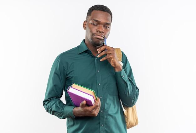 Felice giovane studente afroamericano con zaino in mano libri e penna