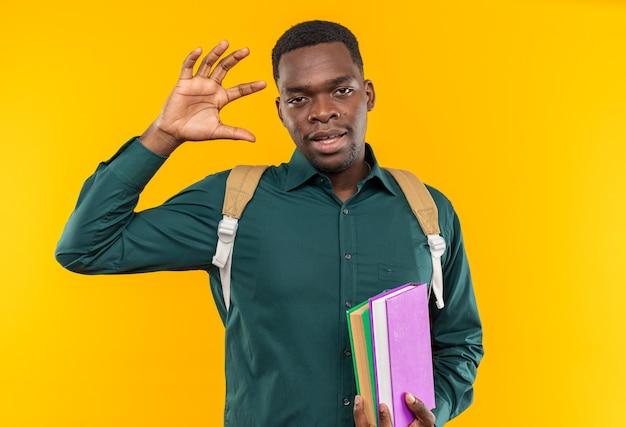Soddisfatto giovane studente afroamericano con zaino in mano libri e alzando la mano