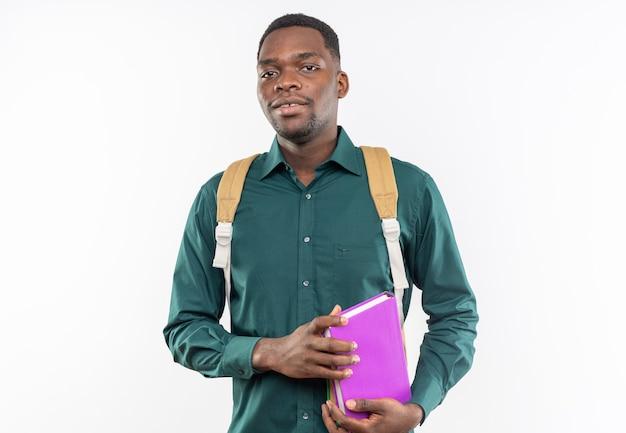 Felice giovane studente afroamericano con lo zaino che tiene i libri