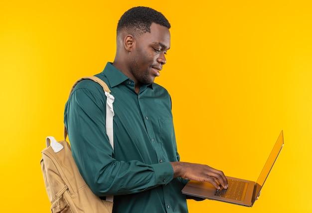 Felice giovane studente afro-americano con lo zaino che tiene in mano e guarda il laptop isolato sulla parete arancione con spazio per le copie