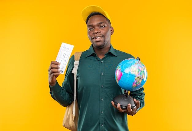 모자와 배낭을 메고 비행기표를 들고 주황색 벽에 복사 공간이 있는 지구본을 들고 기뻐하는 젊은 아프리카계 미국인 학생