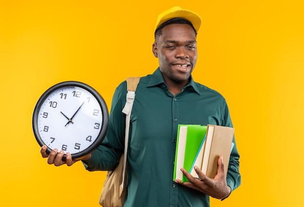 모자와 배낭을 들고 오렌지색 벽에 복사 공간이 있는 책과 시계를 들고 기뻐하는 젊은 아프리카계 미국인 학생