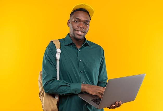 ラップトップを保持しているキャップとバックパックで若いアフリカ系アメリカ人の学生を喜ばせる