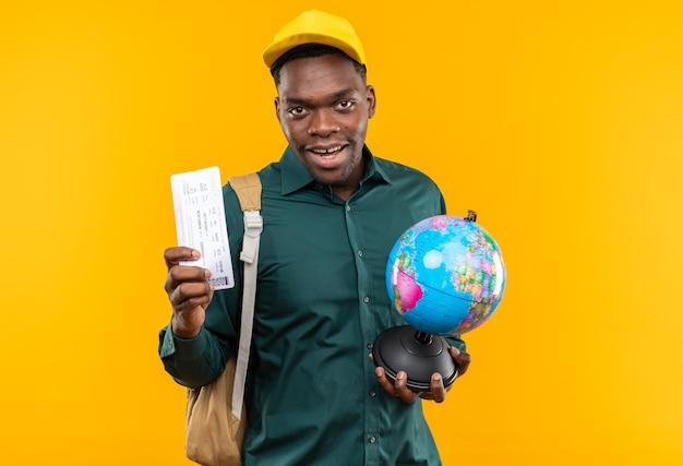 모자와 배낭을 메고 기뻐하는 젊은 아프리카계 미국인 학생은 비행기표와 복사 공간이 있는 주황색 벽에 격리된 지구본을 들고 있습니다.