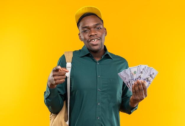 Felice giovane studente afroamericano con berretto e zaino che tiene soldi e indica davanti