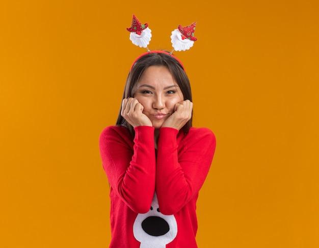 Lieta giovane ragazza asiatica che indossa il cerchio dei capelli di natale con il maglione che mette i pugni sulle guance isolate sulla parete arancione