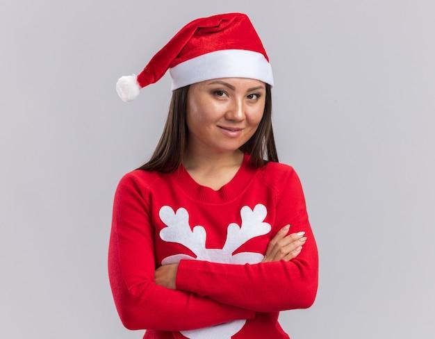 Довольная молодая азиатская девушка в новогодней шапке со свитером, скрещивающим руки, изолирована на белом фоне