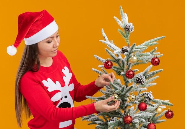 Довольная молодая азиатская девушка в новогодней шапке со свитером украшает елку на оранжевой стене