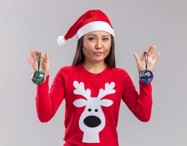 Довольная молодая азиатская девушка в новогодней шапке со свитером, держащая елочные шары на белом фоне