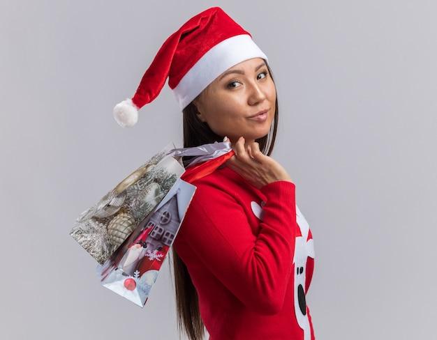 흰색 배경에 고립 된 어깨에 선물 가방을 들고 스웨터와 크리스마스 모자를 쓰고 기쁘게 젊은 아시아 여자
