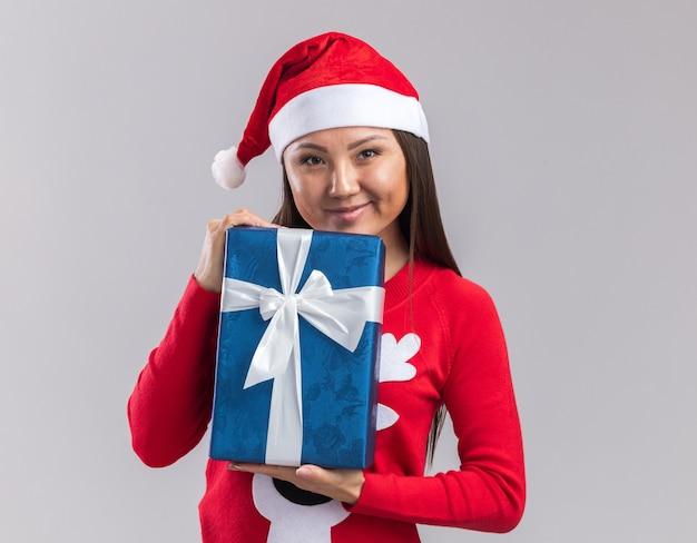 Довольная молодая азиатская девушка в новогодней шапке со свитером, держащая подарочную коробку на белом фоне