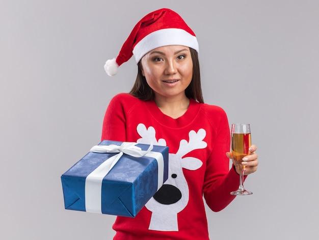 Felice giovane ragazza asiatica che indossa un cappello di natale con un maglione che tiene in mano una confezione regalo con un bicchiere di champagne isolato su sfondo bianco