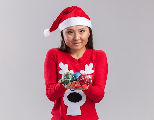흰색 배경에 고립 된 카메라에서 크리스마스 트리 볼을 들고 스웨터와 크리스마스 모자를 쓰고 기쁘게 젊은 아시아 소녀