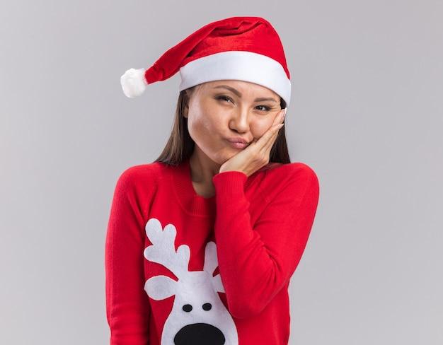 Довольная молодая азиатская девушка в новогодней шапке со свитером, положив руку на щеку, изолированную на белом фоне