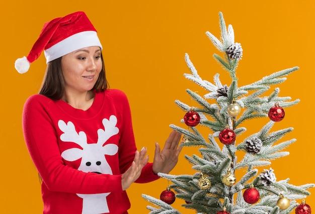 Довольная молодая азиатская девушка в новогодней шапке со свитером стоит рядом с елкой, изолированной на оранжевом фоне