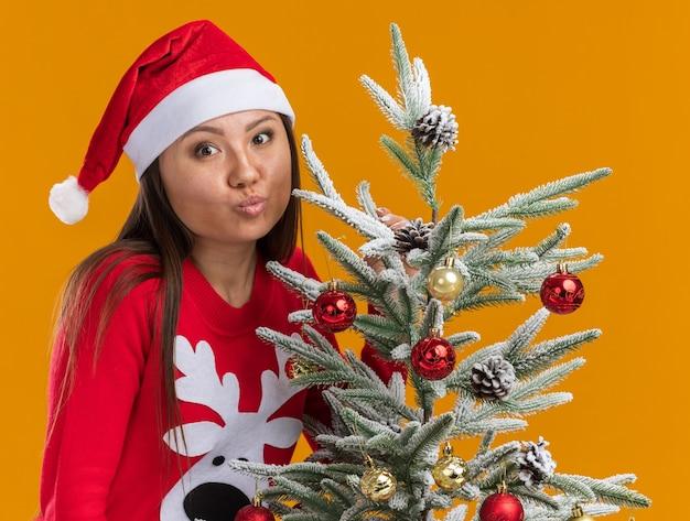 Довольная молодая азиатская девушка в новогодней шапке со свитером стоит возле елки, показывая жест поцелуя, изолированный на оранжевом фоне