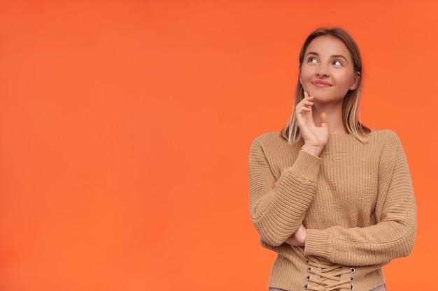 Довольная молодая привлекательная блондинка с короткой стрижкой, нежно улыбаясь, глядя вверх и касаясь лица поднятой рукой, изолирована над оранжевой стеной