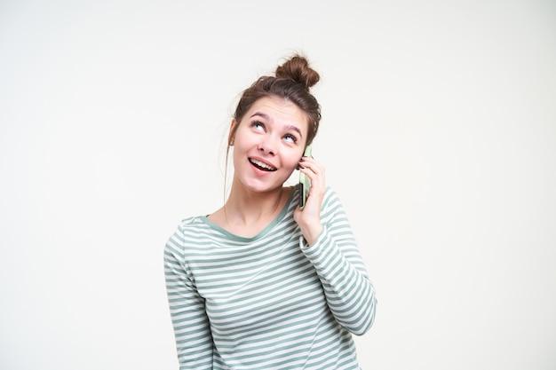Lieta giovane attraente donna bruna dagli occhi azzurri guardando allegramente verso l'alto pur avendo una bella conversazione telefonica, isolata sopra il muro bianco in abbigliamento casual