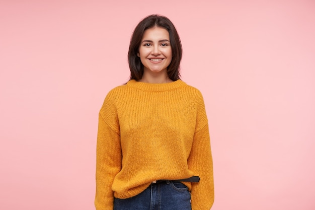 Pleased young attractive brunette woman showing her white perfect teeth while smiling gladly to front, standing over pink wall with hands down