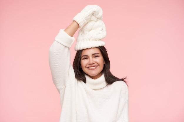 흰색 아늑한 옷에 분홍색 벽 위에 포즈를 취하는 캐주얼 헤어 스타일이 멋지게 웃고 그녀의 머리 위에 손을 유지하는 기쁘게 젊은 매력적인 갈색 머리 여자