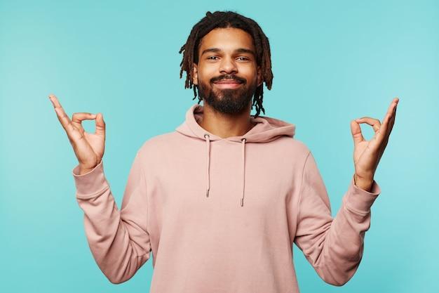 Lieto giovane attraente bruna dalla pelle scura maschio alzando le mani nel gesto mudra e guardando allegramente la fotocamera con un sorriso sincero, isolato su sfondo blu