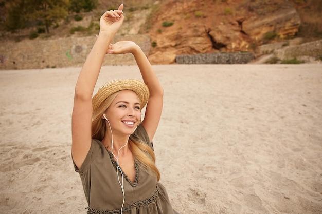 Довольная молодая привлекательная длинноволосая блондинка с естественным макияжем держит руки поднятыми, слушая музыку в наушниках и радостно глядя вверх