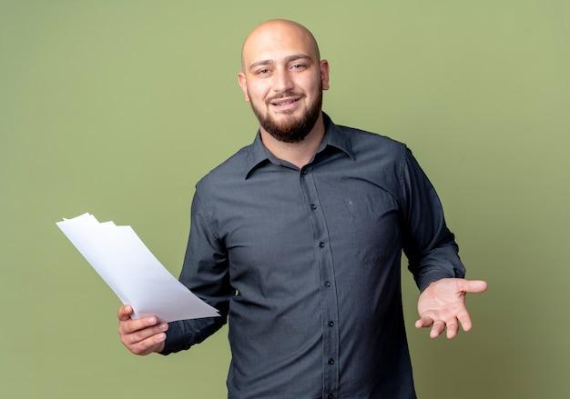 Felice giovane uomo calvo call center in possesso di documenti e mostrando la mano vuota isolata su sfondo verde oliva