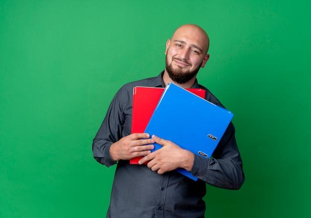 Lieto giovane calvo call center uomo che tiene le cartelle isolate su sfondo verde con copia spazio