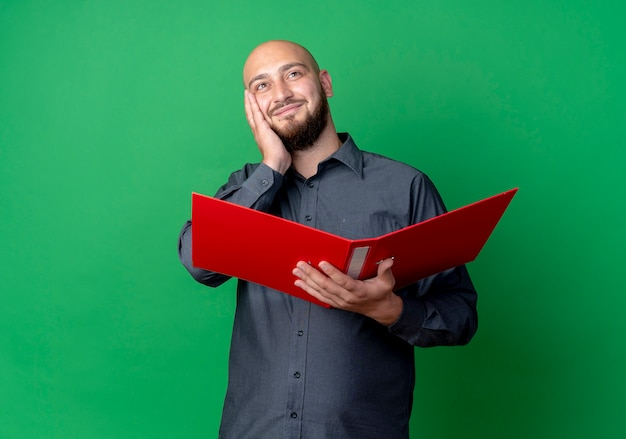 Pleased young bald call center man holding open folder putting hand on face looking up isolated on green background with copy space