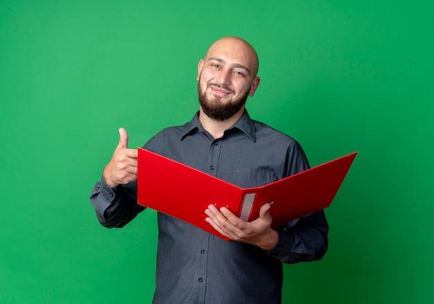 Lieto giovane uomo calvo call center che tiene cartella aperta e che mostra il pollice in alto isolato su sfondo verde