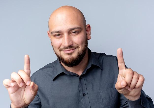 Felice giovane calvo call center uomo che guarda la fotocamera e puntare le dita in alto isolato su sfondo bianco