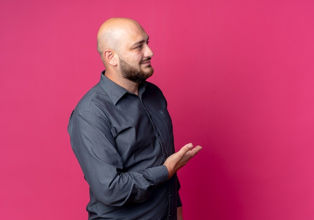Довольный молодой лысый человек из колл-центра смотрит прямо и показывает рукой в сторону, изолированную на малиновом фоне с копией пространства