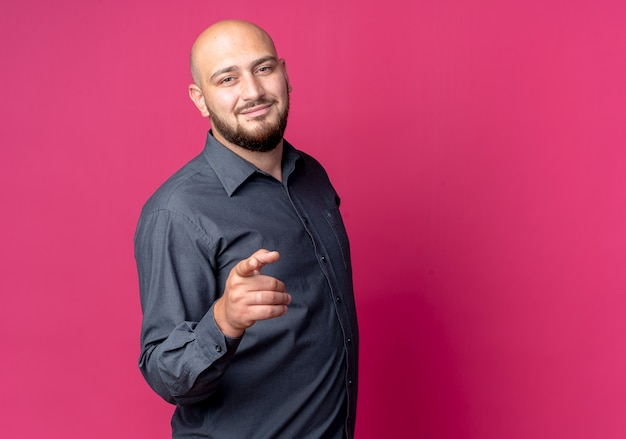 Pleased young bald call center man pointing at camera isolated on crimson background with copy space