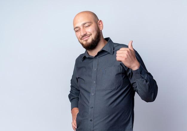 Felice giovane uomo calvo call center che mostra il pollice in alto e mettendo la mano sulla vita isolato su sfondo bianco con spazio di copia