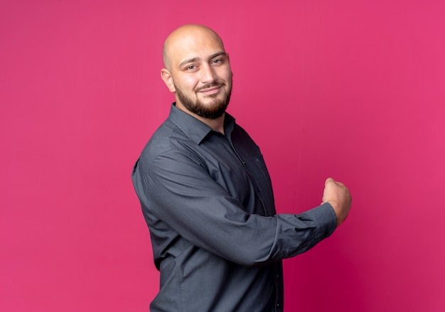 Pleased young bald call center man standing in profile view pointing behind isolated on crimson background with copy space