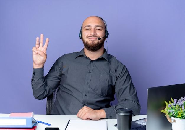 보라색 배경에 고립 된 세 가지를 보여주는 작업 도구로 책상에 앉아 헤드셋을 입고 기쁘게 젊은 대머리 콜 센터 남자