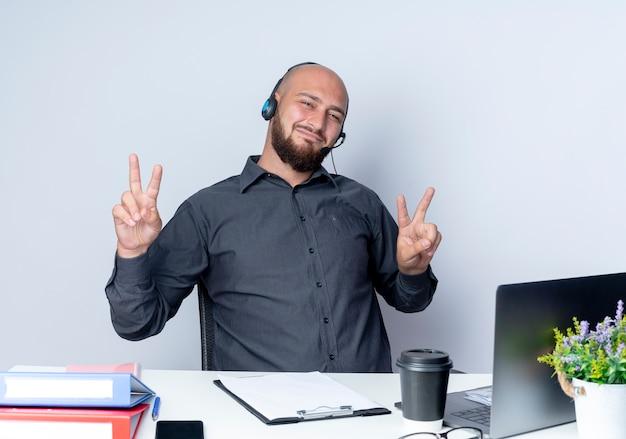 Lieto giovane calvo call center uomo che indossa la cuffia seduto alla scrivania con strumenti di lavoro facendo segni di pace isolati su sfondo bianco