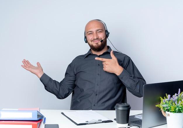 Felice giovane calvo call center uomo che indossa l'auricolare seduto alla scrivania con strumenti di lavoro che mostra la mano vuota e indicando isolato su sfondo bianco