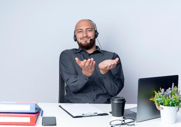 Felice giovane calvo call center uomo che indossa auricolare seduto alla scrivania con strumenti di lavoro che mostra le mani vuote in telecamera isolata su sfondo bianco