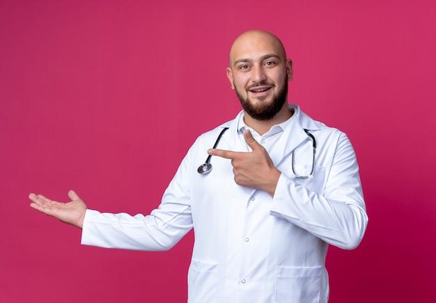의료 가운과 청진기를 입고 기쁘게 젊은 대머리 남성 의사 복사 공간이 분홍색 배경에 고립 된 뭔가 들고 척