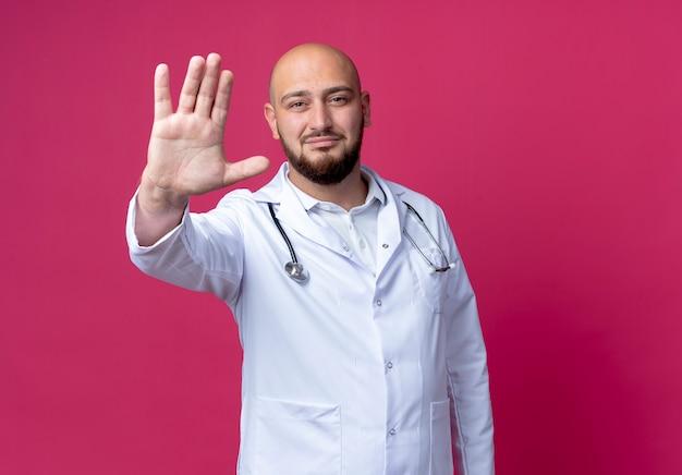 ピンクの壁に隔離された停止ジェスチャーを示す医療ローブと聴診器を身に着けている若いハゲの男性医師を喜ばせる