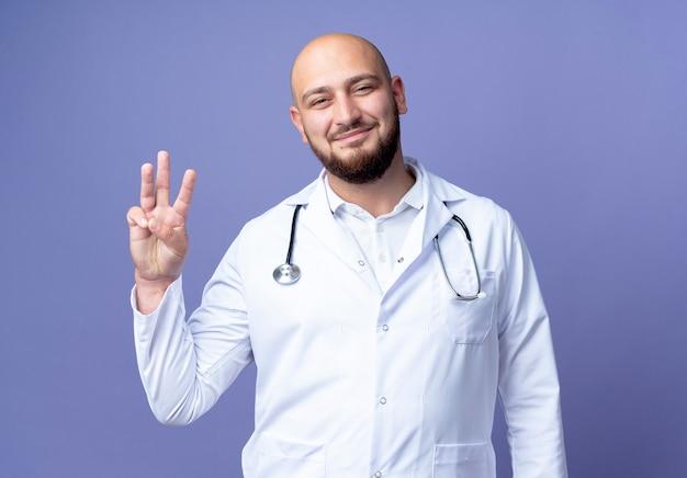 파란색 배경에 고립 된 3을 보여주는 의료 가운과 청진기를 입고 기쁘게 젊은 대머리 남성 의사