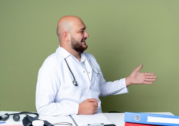 녹색 배경에 고립 된 측면에 손을 들고 의료 도구와 책상 작업에 앉아 의료 가운과 청진기를 입고 기쁘게 젊은 대머리 남성 의사