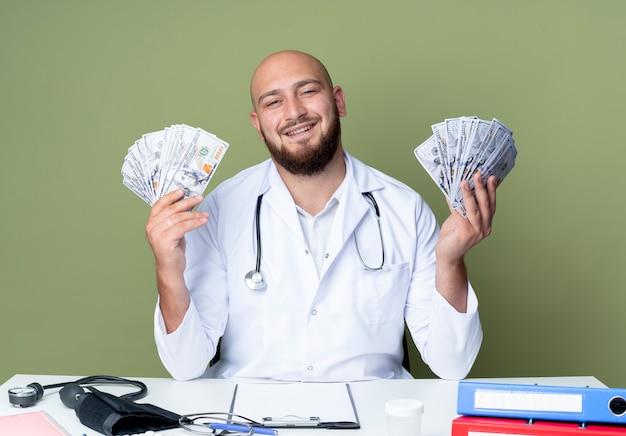 책상에 앉아 의료 가운과 청진기를 입고 기쁘게 젊은 대머리 남성 의사