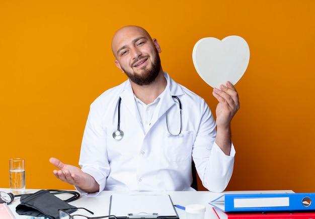 医療用ローブと聴診器を着て仕事机に座っている喜んでいる若いハゲ男性医師
