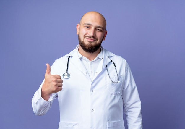 Pleased young bald male doctor wearing medical robe and stethoscope his thumb up isolated on blue background
